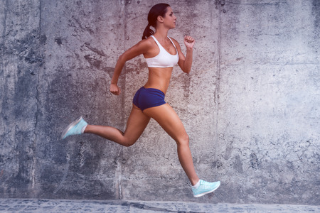 fit: Keep on running.  Full length side view of beautiful young woman in sports clothing running with a concrete wall in the background Stock Photo