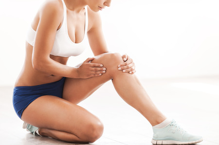 human knee: Physical injury. Cropped image of beautiful young woman in sports clothing touching her injured knee while kneeling on the floor Stock Photo