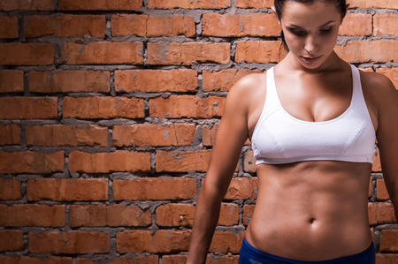 abdominal wall: Trained to perfection. Beautiful young woman in sports clothing looking down while standing against brick wall Stock Photo