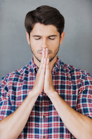hands clasped: Hoping for good. Thoughtful young man holding hands clasped near face and keeping eyes closed while standing against grey background