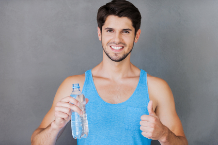 grey water: Refreshing after training. Cheerful young muscular man holding a bottle with water and thumb up while standing against grey background
