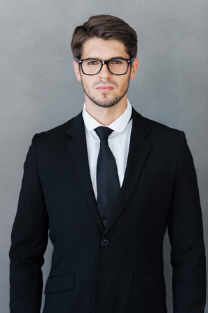 Confident and successful. Confident young man in formalwear looking at camera while standing against grey background Imagens