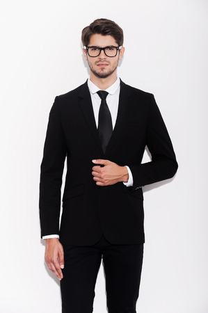 white suit: Making business looking good. Handsome young businessman adjusting his jacket and looking at camera while standing against white background Stock Photo