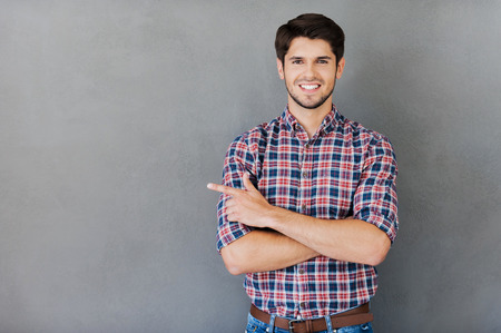 Pointing copy space. Handsome young man pointing away and smiling while standing against grey background
