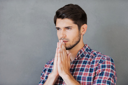 hands clasped: Begging for good. Thoughtful young man holding hands clasped near face and looking away while standing against grey background