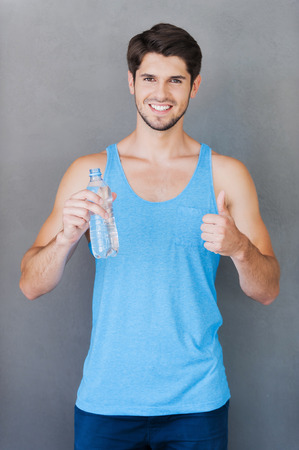 grey water: Fresh and clean water after good training! Smiling young muscular man holding a bottle with water and thumb up while standing against grey background Stock Photo