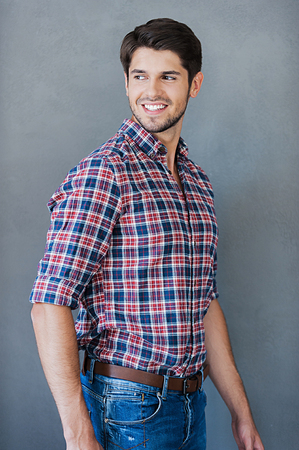looking over shoulder: Cheerful and handsome. Smiling young man looking over shoulder while standing against grey background