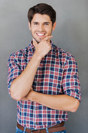 He is full of creative ideas. Cheerful young man holding hand on chin and looking at camera while standing against grey background