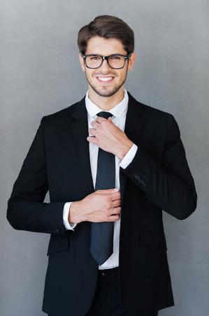 모든 것이 완벽해야합니다. 회색 배경에 서있는 동안 행복 한 젊은 사업가 자신의 넥타이를 조정하고 카메라를 찾고 스톡 콘텐츠