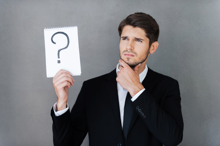 preguntando: En busca de respuesta. joven hombre de negocios pensativo que sostiene bloc de notas con signo de interrogación sobre ella y mirando a otro lado mientras está de pie contra el fondo gris