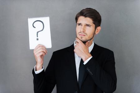 question mark: In cerca di risposta. Riflessivo giovane uomo d'affari azienda blocco note con il punto interrogativo su di esso e guardando lontano, mentre in piedi contro sfondo grigio