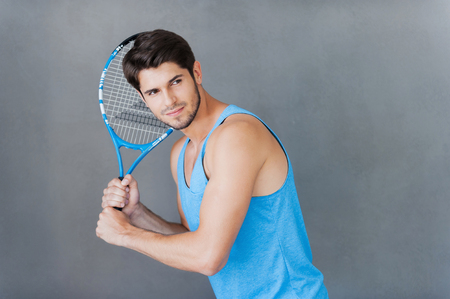only the biceps: Tennis player. Confident young muscular man holding tennis racket while standing against grey backgrounds Stock Photo