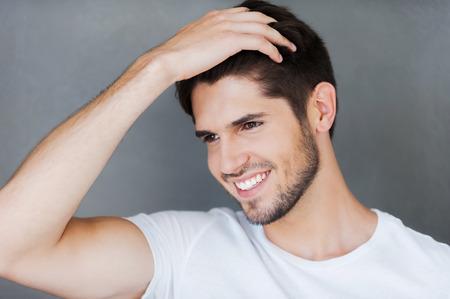 uomini belli: Spensieratezza bello. Felice giovane azienda la mano nei capelli e guardando lontano, mentre in piedi contro sfondo grigio