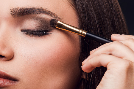 For perfect glance. Close-up of young woman applying eye shadow while standing against black background Stock Photo