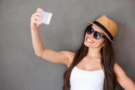 pelo largo: Hora de selfie. Mujeres j�venes alegres que hacen selfie por su tel�fono inteligente y sonriendo mientras est� de pie contra el fondo gris