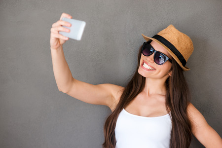 long hair woman: Selfie time. Joyful young women making selfie by her smart phone and smiling while standing against grey background