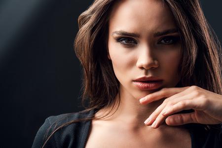 schwarze frau nackt: Schön und geheimnisvoll. Schöne junge Frau berührt ihr Kinn im Stehen vor schwarzem Hintergrund