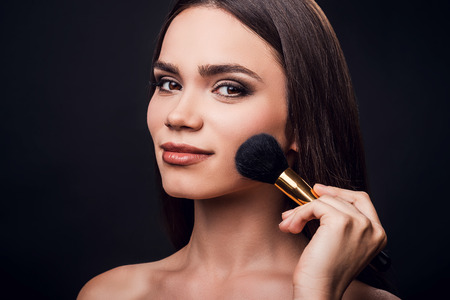 cheekbones: Emphasizing her cheekbones. Smiling young woman holding make-up brush near her cheek while standing against black background
