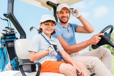 little man: Two smiling golfers. Happy young man and his little son sitting in golf cart and looking at camera