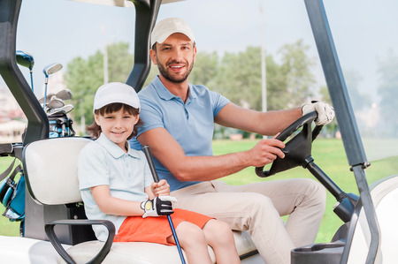 cart: Father and son in golf cart. Smiling little boy sitting in golf cart while his father driving it Stock Photo