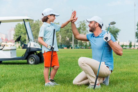 golf cart: My little winner! Cheerful young man and his son giving high-five to each other while standing on the golf course Stock Photo