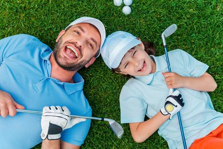 幸せなゴルファー。陽気な少年と父親のゴルフクラブを押しながら緑の芝生に横になっている笑顔の平面図