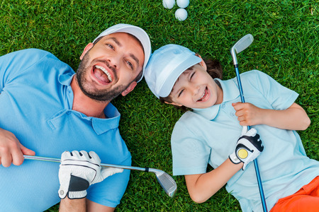 golf man: Happy golfers. Top view of cheerful little boy and his father holding golf clubs and smiling while lying on the green grass