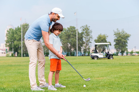 Sharing with golf experience. Cheerful young man teaching his son to play golf while standing on the golf course 스톡 콘텐츠