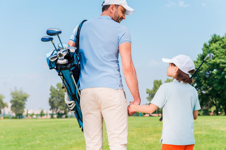 golf cap: It was a great game! Rear view of young man and his son holding hands and looking at each other while walking on the golf course