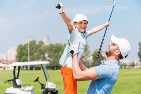 Alegría de gran juego. Hombre joven emocionado que recoger a su hijo mientras está de pie en el campo de golf Foto de archivo - 41746652