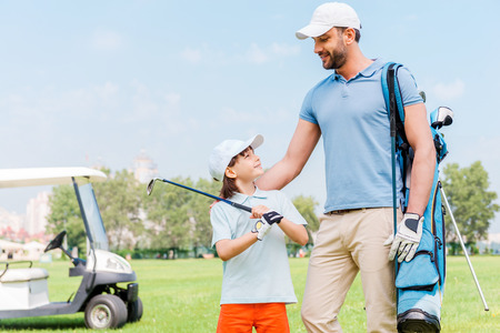 golf cart: Enjoying great game together. Smiling young man and his son looking at each other while standing on the golf course Stock Photo