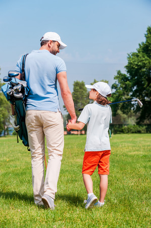 holding hands while walking: Confident golf players. Rear view of young man and his son holding hands and looking at each other while walking on the golf course Stock Photo