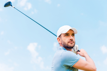 golf glove: Confident golfer. Low angle view of serious young man playing golf while standing outdoors Stock Photo