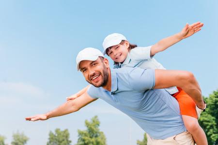 おんぶ。屋外に立っている間彼の息子をピギーバック笑顔の若い男