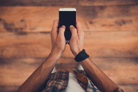 terra arrendada: Ficar em contato. Vista de cima do homem que prende o telefone inteligente em pé no chão de madeira