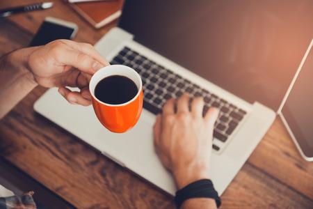 新鮮なコーヒーの素晴らしいアイデア。トップ ビューとしてのラップトップに取り組んで、彼の職場に座って一杯のコーヒーを保持しています。