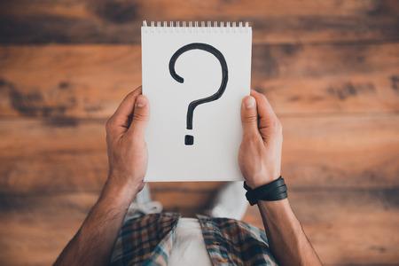 preguntando: Busca respuestas. Vista superior del hombre celebración bloc de notas con signo de interrogación sobre ella mientras está de pie en el suelo de madera