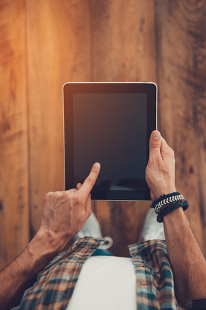 digital tablet: Technologies make life easier. Top view of man using digital tablet while standing on the wooden floor Stock Photo