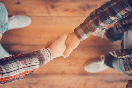 man: Men shaking hands. Top view of two men shaking hands while standing on the wooden floor