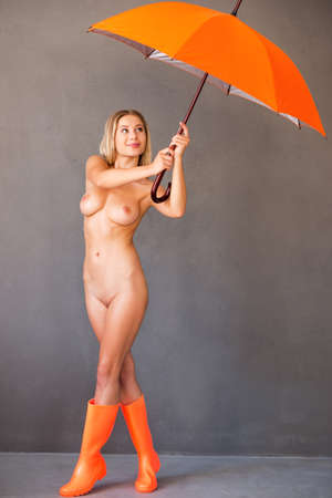 Feeling free and dry. Beautiful young naked woman in orange gumboots holding umbrella and smiling while standing against grey background Stock Photo