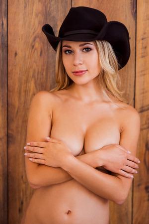 mujer desnuda: Belleza en el sombrero de vaquero. Mujer sin camisa joven hermosa en sombrero de vaquero que cubre sus pechos con las manos y mirando a la cámara mientras está de pie contra el fondo de madera