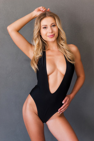 sex pose: Confident in her perfect body. Attractive young blond hair woman in black swimwear posing in front of grey background