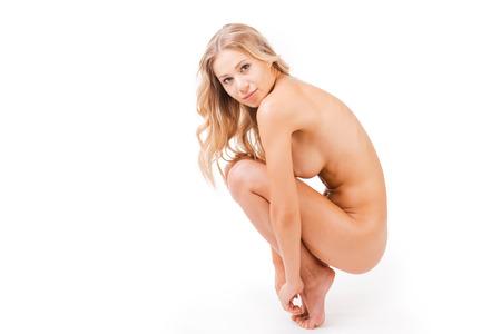 beaux seins: Beaut� pure. Vue de c�t� de la belle jeune femme nue regardant la cam�ra accroupi devant le fond blanc