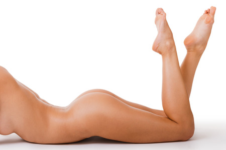 woman naked body: Perfect curves. Close-up of beautiful young naked woman with perfect body lying on her front and keeping feet up Stock Photo