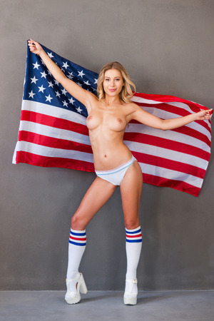 young nude woman: Young and free. Beautiful young shirtless woman holding American flag while standing against grey background