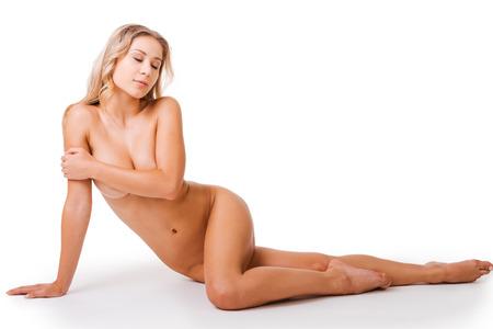 donna nuda: Nuda bellezza. Giovane e bella donna nuda che copre il seno con la mano e tenendo gli occhi chiusi, mentre seduto sul pavimento e di fronte alla sfondo bianco