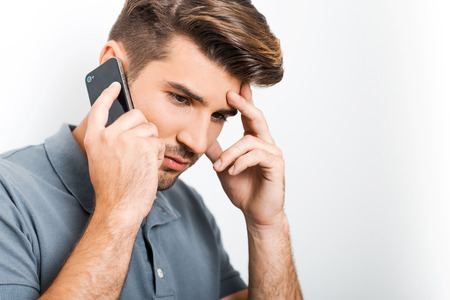 bad news: Bad news. Depressed young man talking on the mobile phone and touching face with hand while leaning at the wall Stock Photo