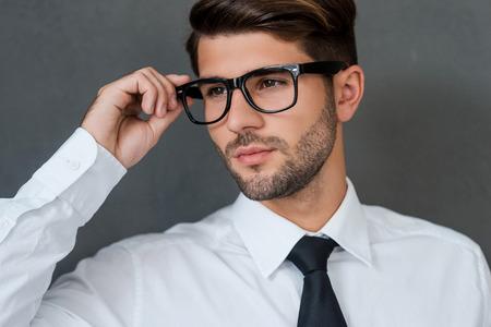 beau mec: Confiant et beau. Confiant jeune homme d'affaires ajustant ses lunettes et regarde au loin en se tenant debout sur fond gris Banque d'images