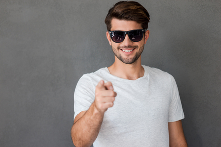 bel homme: I choose you! Happy young man pointing you and smiling while standing against grey background
