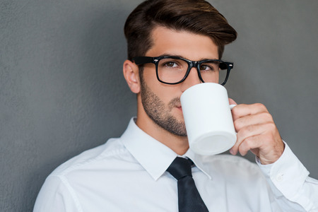 Inspired with cup of fresh coffee. Confident young man in shirt and tie drinking coffee and looking away while standing against grey background
